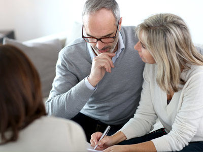 A couple discuss a contract of sale with their conveyancer