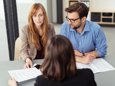 A couple discusses their investment loan options with a finance broker